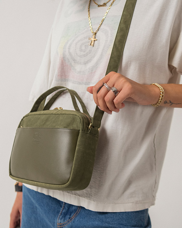 An Ivy Green Orion Crossbody bag on a woman's side